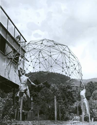 1949 Summer Institute, Buckminster Fuller, Architecture. Pictured: Jeffery Lindsay (sunglasses), Joseph Manulik (behind Lindsay), Ysidore Martinez (behind Caviani), Harold Young (cap), Louis Caviani (far right). They are holding: dome of thirty-one-great circle necklace structure of tubular beads and continuous internal cable net. Constructed in Chicago, 1948-1949. Reconstructed at Black Mountain College, Summer 1949. Double heat-sealed pneumatic transparent skin (not pictured) tested at Black Mountain College. Photographer: Masato Nakagawa. Courtesy Western Regional Archives
