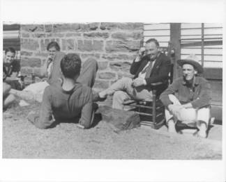 Blue Ridge campus scene at Black Mountain College. Although several BMC community members are pictured, the only ones identified are John Rice (sitting in the rocking chair) and student David Bailey (wearing a hat). Courtesy of Western Regional Archives.