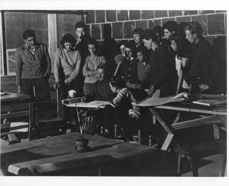 """Josef Albers' drawing class, Black Mountain College. From the back of the photograph: """"Albers, seated; Eva Zhitlowsky, seated at Albers's left; Faith Murray, standing behind Albers, against wall, with bangs and glasses; Claude Stoller, third from right, against wall."""" Photograph likely taken at the Blue Ridge campus. Courtesy of Western Regional Archives."""