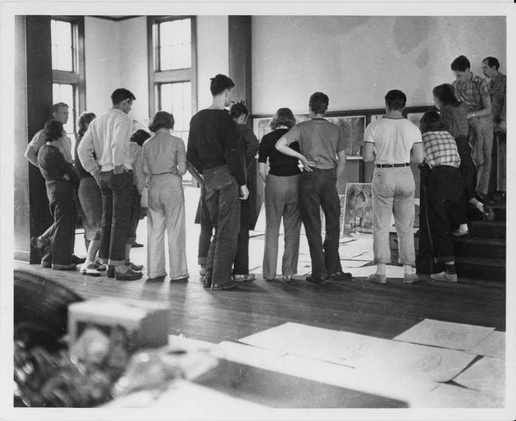 "Josef Albers's Drawing Class, Black Mountain College, ca. 1939-1940. From the back of the photograph: ""left to right (incomplete listing): Charles Kessler (extreme left, hand on hip), Hope Stephens (in straight skirt and the saddle shoes), Betty Brett (leaning forward, standing in fron of male student with pencil behind his ear), Frances Kuntz (beside Brett), Dick Andrews (with pipe), Fred Stone (in front of Andrews), Mimi French (in dark sweater and light collar), Robert De Niro (hand on hip, moccasins), Bela Martin (t-shirt and sneakers), Martha McMillan (light plaid shirt and sneakers with dark socks), Harriet Englehardt (dark plaid shirt, light socks, standing on second and third steps), Rudolph Haase (sitting on banister)."" Photograph likely taken at the Blue Ridge campus. Courtesy of Western Regional Archives."