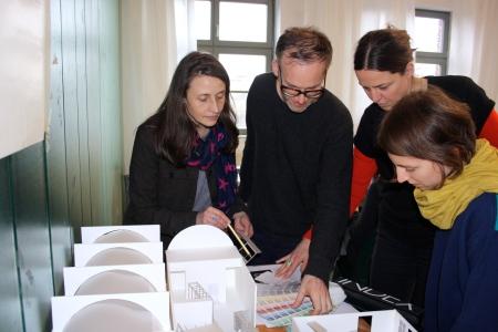 Teambesprechung der ArchitektInnen Andrea Hofman, Florian Stirnemann, Frauke Gerstenberg and Claire Mothais (vo li na re) über dem BMC-Architekturmodell im Büro von raumlaborberlin.
