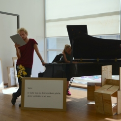 Photo by Elizabet Damyanova. Tobias Shaw Petersen reading while Desiree Vaksdal plays the piano.