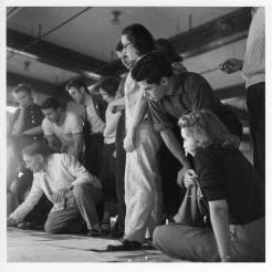 """Josef Albers's Drawing Class, Black Mountain College, ca. 1939-1940. From the back of the photograph: """"left to right: Hope Stephens (chin in palm of hand), Bela Martin (light t-shirt), Josef Albers (kneeling), Fred Stone (sport coat), Bettey Brett (rolled-up jeans), Robert De Niro (striped t-shirt), Eunice Shifris (glasses), Martha McMillan (plad shirt, behind Shifris), Claude Stoller (dark shirt, leaning forward), Mimi French (on the floor, holding glasses)"""". Courtesy of Western Regional Archives."""